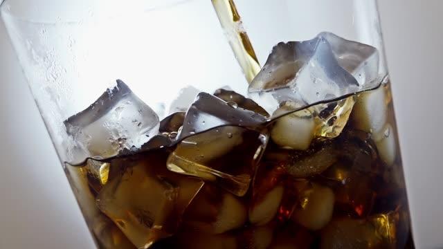 ゆっくりとした動きで氷のグラスにアイスティーを注ぐ。 - 茶色点の映像素材/bロール
