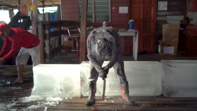 ice worker cutting off blocks of ice - cutting stock videos & royalty-free footage