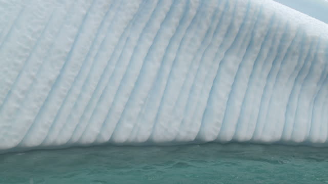 iceberg. 'bubble' grooves, made from ice melting and air bubbles trapped taking the shortest route to the surface and carving grooves. orne island. antarctic peninsula - antarctica iceberg stock videos & royalty-free footage