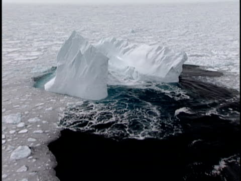 vidéos et rushes de low aerial, iceberg in pack ice, labrador sea, labrador, canada - iceberg bloc de glace