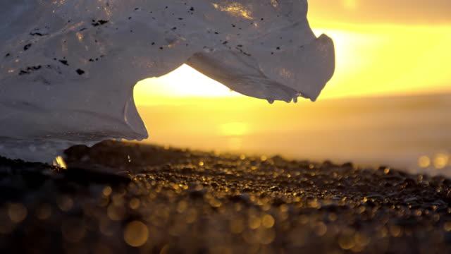 slo-mo-eisberg schmilzt bei sonnenuntergang - melting stock-videos und b-roll-filmmaterial