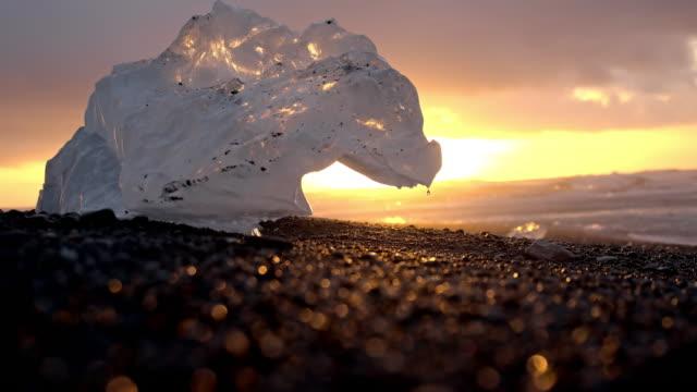 vídeos y material grabado en eventos de stock de slo mo iceberg derrite sobre la playa negro - melting