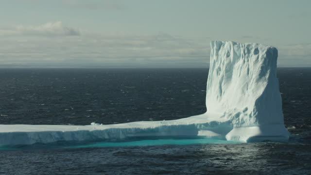 iceberg towers over the ocean surface - arktis stock-videos und b-roll-filmmaterial
