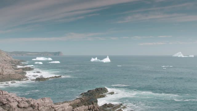 WS Icebergs floating in sea, waves splashing on rocks / St. John's, Newfoundland and Labrador, Canada