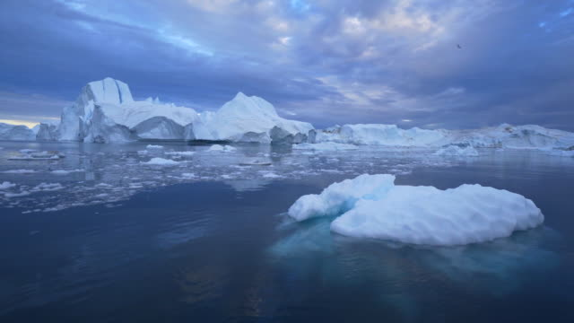 icebergs floating on disko bay against cloudy sky - inlet stock videos & royalty-free footage