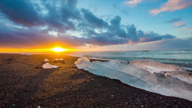 t/l 8k icebergs on black beach at sunrise - iceland stock videos & royalty-free footage