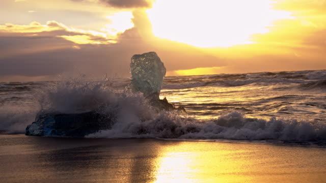 Isberg på svarta stranden i solnedgången