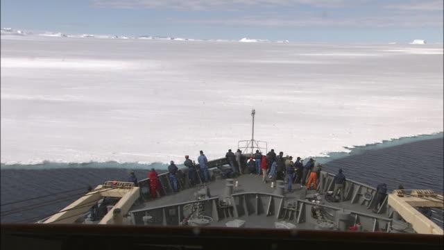 icebreaker ship 'shirase' sails towards ice cut to bow pushing through ice antarctic - 氷点の映像素材/bロール