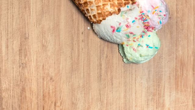 ice-cream cone melting on wooden background - waffled stock videos and b-roll footage