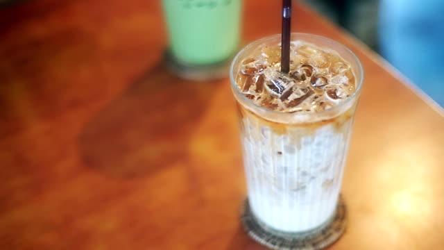 Iskallt kaffe latte och Iced grönt te latte på träbord i kafé.