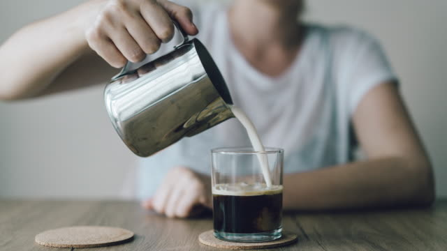 iced coffee with cream being poured in - pouring milk stock videos & royalty-free footage