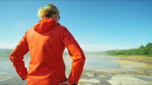 vídeos de stock, filmes e b-roll de iceland geysir strokkur female backpacker golden circle volcanic - gêiser strokkur