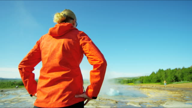 vídeos de stock, filmes e b-roll de iceland geysir strokkur female hot springs hiker tourist - gêiser strokkur