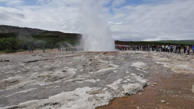 vídeos de stock, filmes e b-roll de iceland haukadalur people wait for strokkur geyser to erupt pan.mov - gêiser strokkur