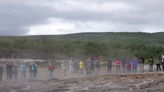 Iceland Haukadalur Strokkur geyser with tourists watching eruption