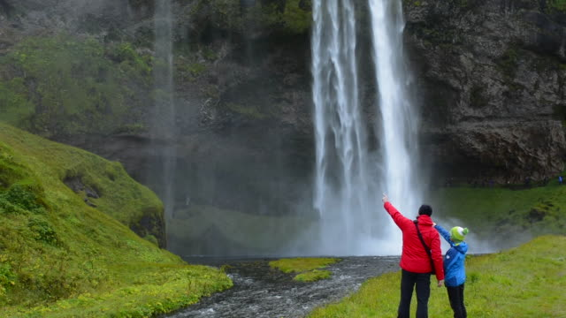 iceland seljalandsfoss waterfalls famous water falls in south iceland with 180 feet or 60 metres fall of water with father showing son - pointing stock videos & royalty-free footage