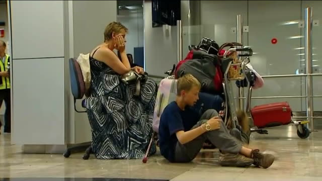 britons begin travelling home goodings seated next her children and pile of luggage - cenere video stock e b–roll