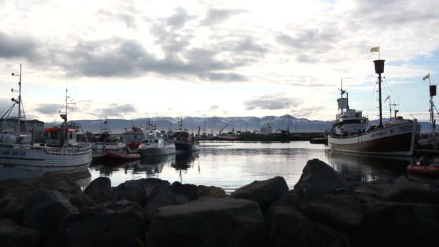 Icelandic harbor Husavik with fishing boats at dusk