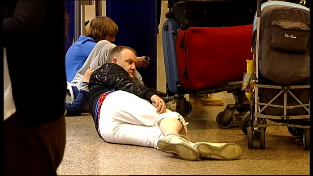 flights back to normal holidaymakers lying on and sitting on concourse floor surrounded by luggage trolleys passengers sleeping adn sitting in... - cenere video stock e b–roll