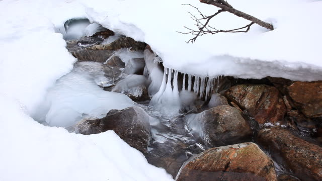 Icicles and a snowy ledge hang over a rocky stream.