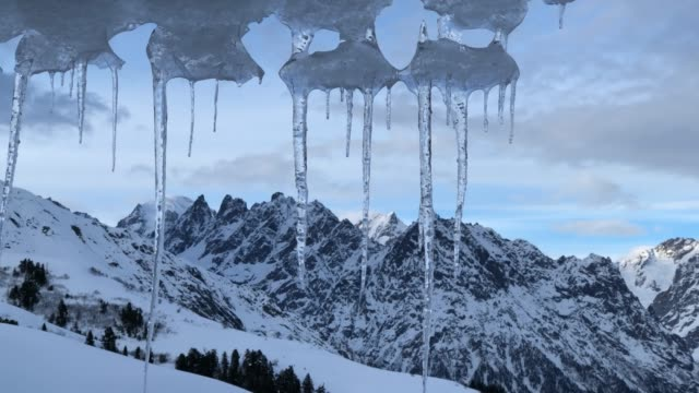 icicles from roof with view of mountains - icicle stock videos & royalty-free footage