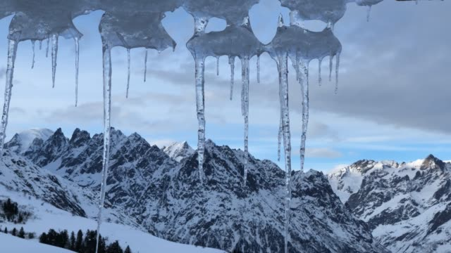 icicles from roof with view of mountains - icicle stock videos and b-roll footage