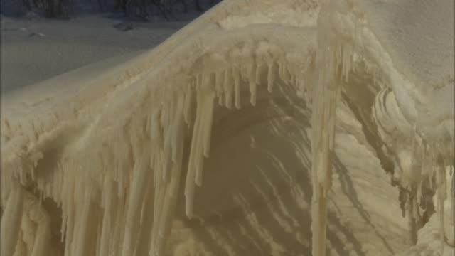 vídeos de stock, filmes e b-roll de icicles hang from an arched hood of snow. - pingente de gelo