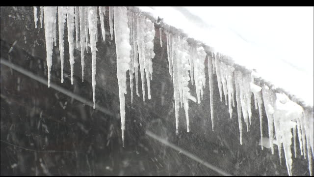 icicles hang from eaves during heavy snow-fall - eaves stock videos and b-roll footage