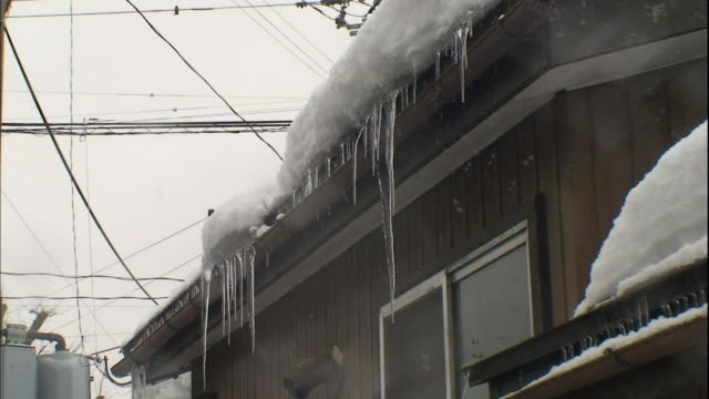 icicles hang from the eaves of a house as it snows. - eaves stock videos and b-roll footage