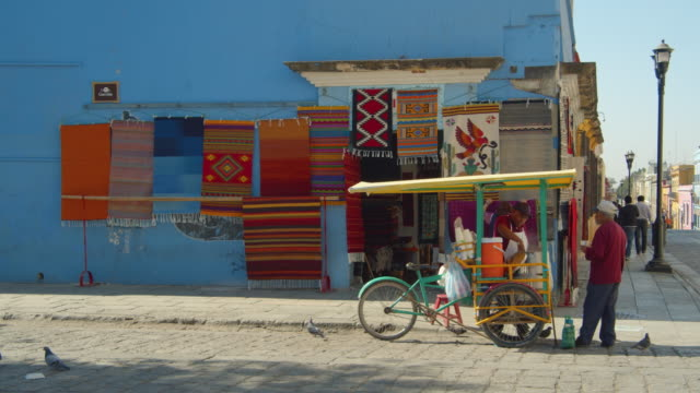 iconic image of a mexican colonial style city with colorful short houses. fabrics shop with hanging printed carpets and street food. oaxaca de juarez at macedonio alcala street b-roll - mexiko stock-videos und b-roll-filmmaterial