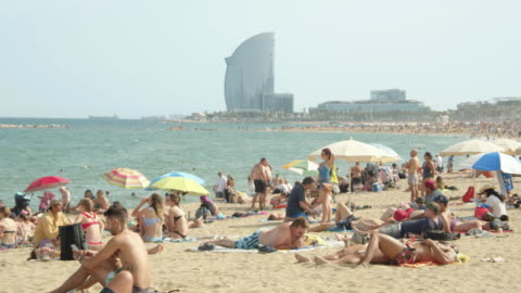 iconic image of barcelona beach at spain. w hotel on the background. people enjoying sunny day at barceloneta - sunbathing stock videos & royalty-free footage
