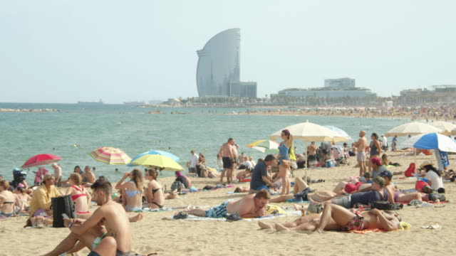 iconic image of barcelona beach at spain. w hotel on the background. people enjoying sunny day at barceloneta - tourist stock videos & royalty-free footage