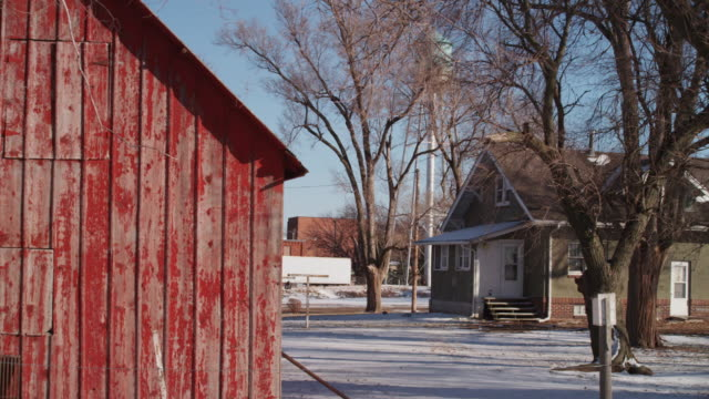 iconic small town scene with weathered red barn and small home in the background. - weathered stock videos & royalty-free footage