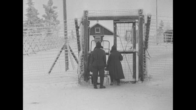 Icy barbed wire with barracks beyond / VS Russian POWs moving metalframe bunk beds through gate / a Finnish guard closes gate door with close view of...