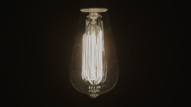 Idea Concept Vintage light bulb turns on with black background