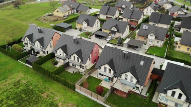 vidéos et rushes de maisons familiales identiques dans une rangée - vue aérienne - lotissement