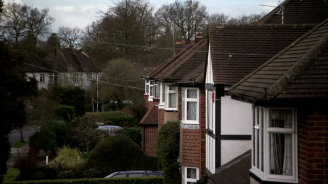 identical houses line a street in rayners lane, london. available in hd. - doppelhaus stock-videos und b-roll-filmmaterial