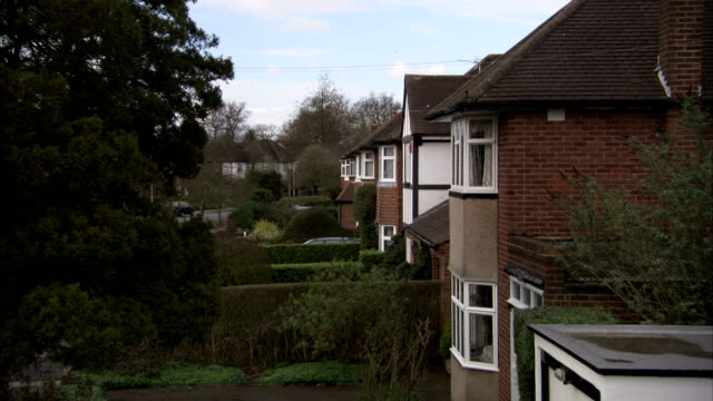 Identical semi-detached houses line a street in Rayners Lane, London. Available in HD.