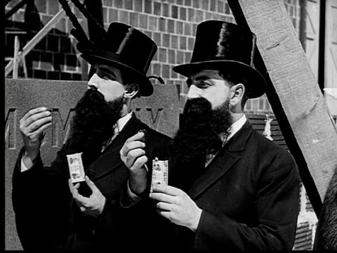 vidéos et rushes de 1924 b&w ms identical twin men in top hats and long black beards eating candy simultaneously  - effet miroir