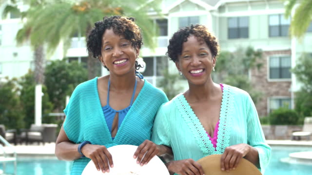 identical twin sisters by pool, holding hats - twin stock videos & royalty-free footage