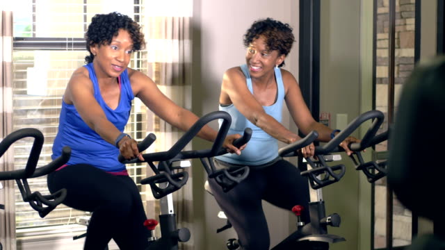 identical twin sisters exercising at gym on bikes - identical twin stock videos & royalty-free footage