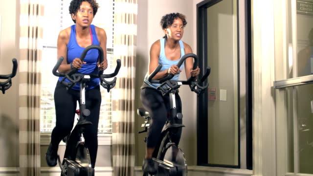 自転車でジムで運動する同一の双子の姉妹 - そっくりさん点の映像素材/bロール