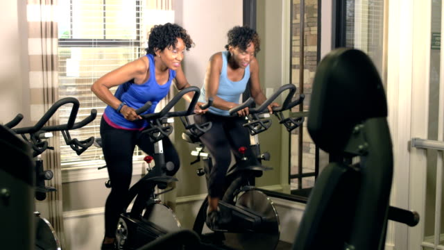 identical twin sisters exercising at gym on bikes - sister stock videos & royalty-free footage