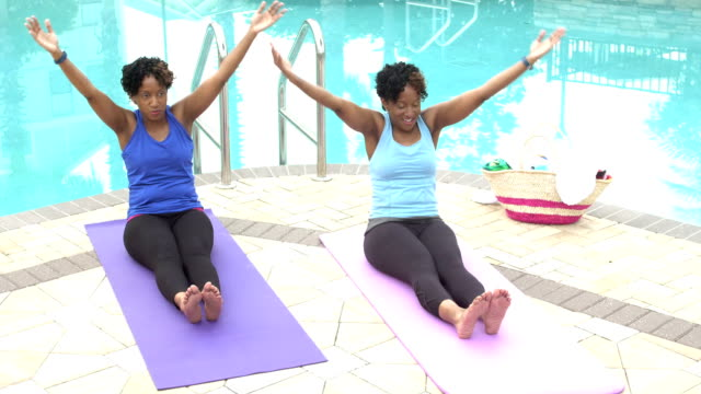 identical twin sisters exercising by pool, stretching - identical twin stock videos & royalty-free footage