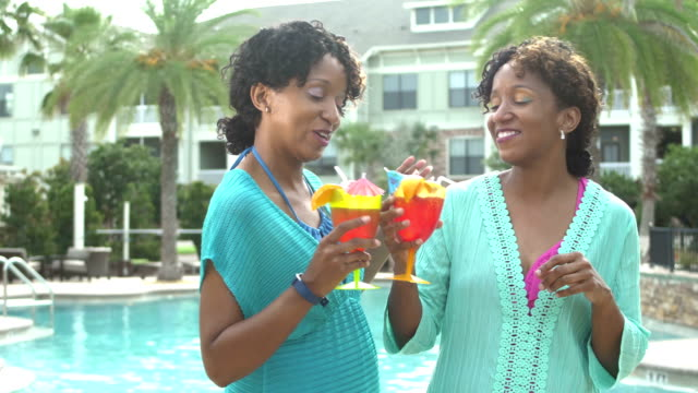 identical twin sisters pool with tropical drinks - identical twin stock videos & royalty-free footage