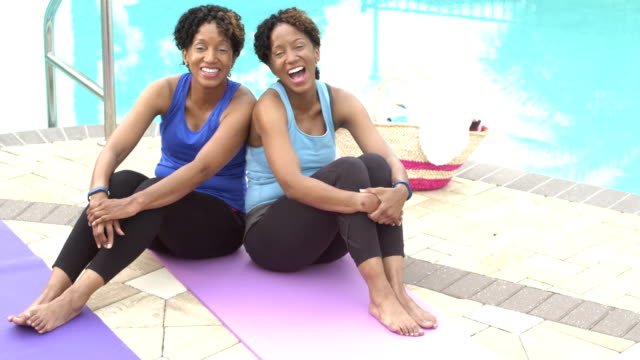 identical twin sisters sitting on exercise mats by pool - identical twin stock videos & royalty-free footage
