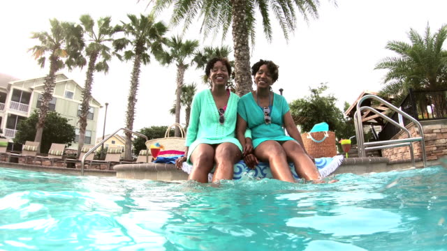 identical twin sisters sitting on side of pool - identical twin stock videos & royalty-free footage