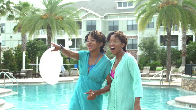 identical twin sisters walking by swimming pool - identical twin stock videos & royalty-free footage