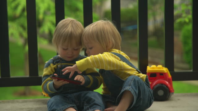 identical twin toddlers play with smartphone - identical twin stock videos & royalty-free footage