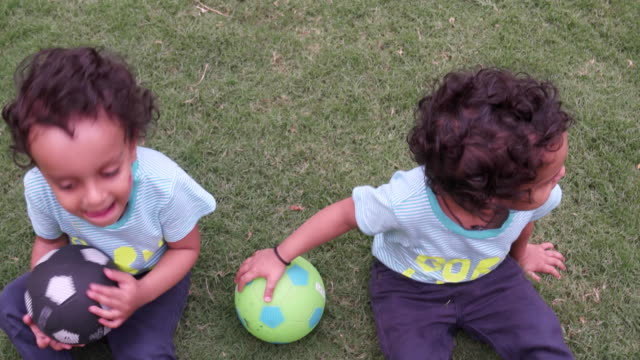 identical twins sitting and playing with footballs in a park - identical twin stock videos & royalty-free footage